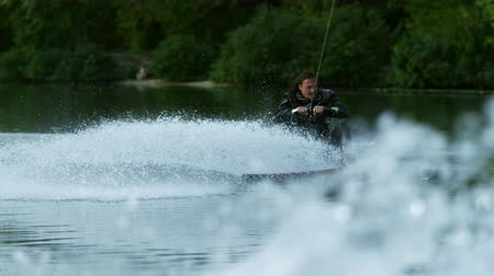 lancha : Wakeboarder making tricks on waves during movement in slow motion. Joyful man riding wakeboard in water splash. Athlete water skiing and have fun. Extreme water sports Vídeos