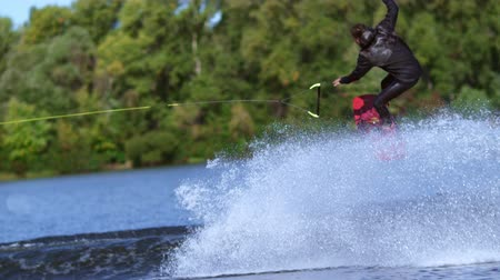 narciarz : Man wakeboarder making tricks on water. Rider falling down in water. Water skier failing. Extreme failing. Extreme sport lifestyle. Athlete on wakeboard falling during training Wideo