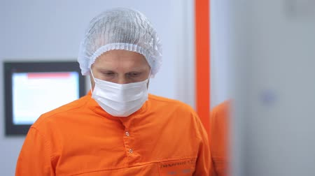 steril : Portrait of thoughtful lab worker in orange uniform. Closeup of confident scientist in orange protective suit and mask on face. Factory worker face mask