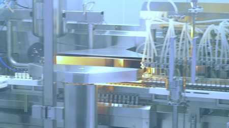 pharmaceuticals : Pharmaceutical manufacturing machine at factory. Drugs manufacturing line. Medical ampoules production line at pharmacy plant. Conveyor belt at pharmaceutical plant