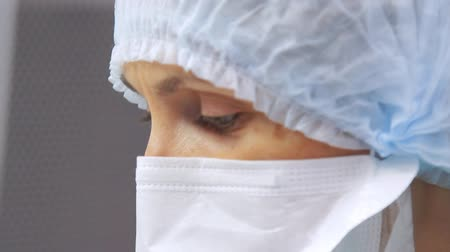lab employee : Female scientist portrait. Close up of laboratory worker face in protective mask looking away. Doctor face in mask Stock Footage