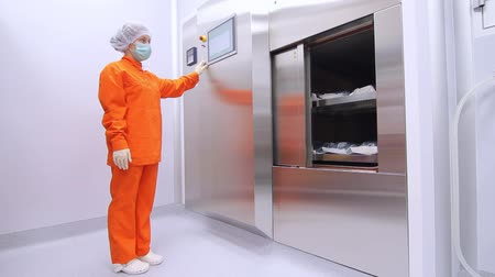 frigorífico : Woman in orange sterility suit using touch screen panel to close refrigerator storehouse at pharmaceutical factory. Female worker in uniform using automated closing warehouse in pharmacy factory.