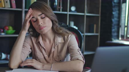woman working : Tired business woman working with headache in home office. Stressed businesswoman upset by bad financial report. Tired woman leaning back at workplace. Female employee thinking about work in office