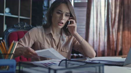 nerves : Business woman calling on mobile phone in startup office. Worried businesswoman try to find documents among papers on table. Stressed manager working in office. Hurry woman looking paper at workplace Stock Footage