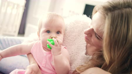 anfíbio : Beautiful baby girl sitting in mother embrace. Young mother with little baby in pink dress. Infant gnawing green toy. Mom with child playing together. Toddler girl with toy in mouth