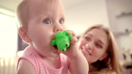 toad : Cute baby girl with toy. Toddler gnawing green toy frog. Little child eating rubber toy. Sweet child playing at home. Infant baby looking around. Baby lifestyle. Happy loving family