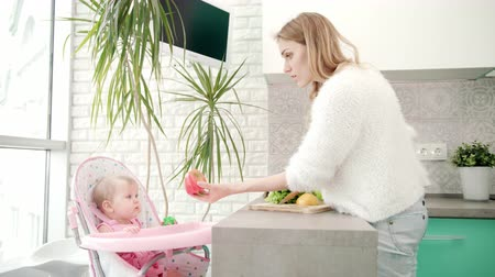 pimentas : Pretty woman cooking healthy food with baby. Mom preparing baby food. Mother cook healthy eating for little child in baby chair. Healthy diet for little child