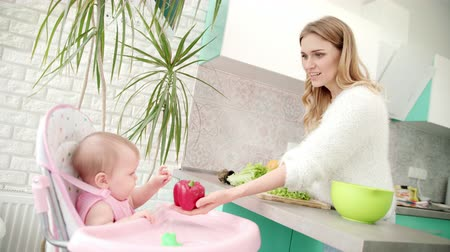akşam yemeği : Mother with baby on kitchen. Healthy baby food. Mom giving red pepper to child in baby chair. Beautiful woman with daughter cooking vegetables. Baby with mother tasting fresh pepper on white kitchen