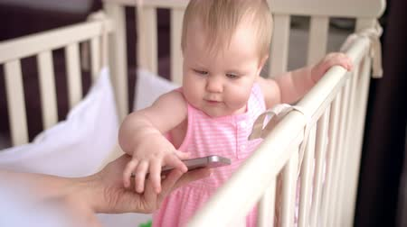 cradle : Cute baby in crib touch smartphone. Child with mobile phone in crib. Female hand give infant touch screen mobile. Baby technology concept