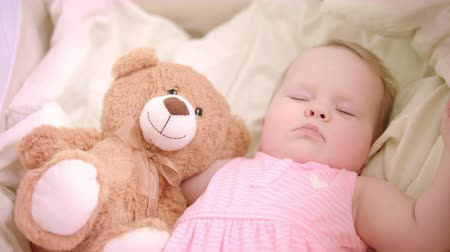 suçsuzluk : Sweet baby girl sleeping with toy in crib. Close up of infant sleeping in cot. Beautiful toddler sleeping with toy bear. Sweet bedtime. Little girl dream in bed. Adorable childhood. Tired baby relax