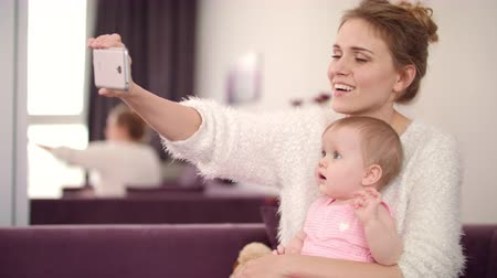 selfie girl : Selfie mom and daughter at home. Mother with baby taking selfie photo on smartphone at cozy home. Beautiful woman with child taking phone photo