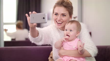 filha : Beautiful woman making selfie with baby. Mom making selfie photo with toddler girl. Sweet motherhood. Mother taking mobile photo with child. Mother love. Woman photo with kid