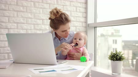 ödev : Working mom with child on table. Business woman with baby working on laptop. Working together with kid. Businesswoman holding toddler girl on hand. Female home work. Woman freelancer at cozy home Stok Video