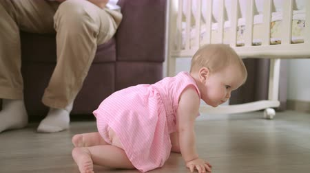 suçsuzluk : Baby crawling on floor at home. Happy family concept. Cute baby girl crawl in home with parents. Adorable child walking on floor. Toddler walking in home. Sweet childhood