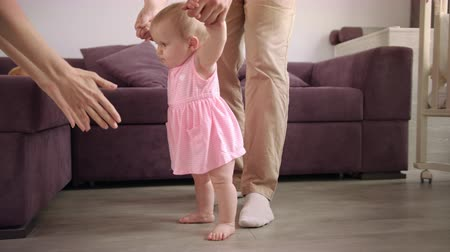 learning to walk : Baby first steps. Parents learning walk kid. Father holding child hands. Baby walking at home. Family support little kid. Baby learning to walk Stock Footage