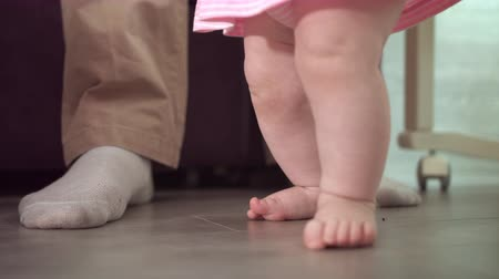 step : Infant feet learning walk. Close up of baby first step with father support. Daddy learning walk little baby. Little steps at home. Parent support concept. Baby feet walking on floor