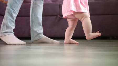 que apoia : Little baby feet walking on floor with parent support. Close up of mother learning child walking. Kid feet steps at home. Little child learn to walking. Baby steps with mom. Toddler doing first step
