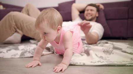 isteyen : Little baby want crawling on floor. Father holding toddler girl dress. Daddy playing with daughter at home. Father holding walking child. Dad have fun with baby. Beautiful toddler try crawl on floor Stok Video