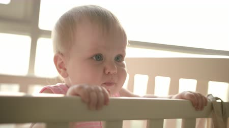 szopka : Cute baby standing in cot. Beautiful child playing in bed. Portrait of little girl standing in baby room. Cute childhood. Sweet kid looking mom. Toddler girl in crib Wideo