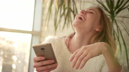 муравей : Smiling woman texting sms on smartphone. Happy woman holding phone ant typing message. Internet connection on smartphone. Sweet girl typing phone. Joyful woman texting mobile