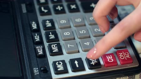 despesas : Business woman hand using calculator at office. Close up of financial adviser working with calculator. Business accounting calculating money profit. Calculator on background of dollar banknotes Vídeos