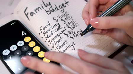 despesas : Woman calculate family budget on calculator and writing in notebook. Family budget calculation. Home accounting and domestic finances managing. Family finance concept