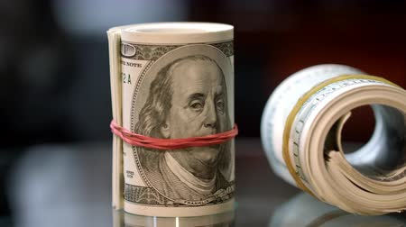 rentável : Cash money rolls on table. Rotating rolls of hundred american dollar bills with rubber bands. Business success and commercial activity Vídeos
