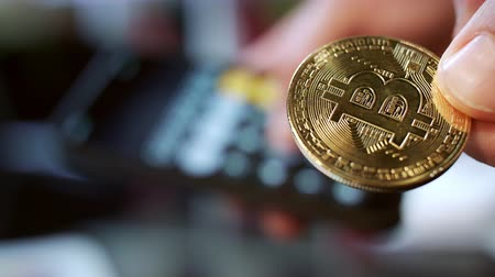 kalkulačka : Investment in bitcoin cryptocurrency business. Man holding gold bitcoin coin. Global blockchain technology. Man calculating profit from bitcoin mining, Cryptocurrency online transactions