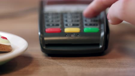 вводить : Pos terminal payment in cafe. Woman hand enter pin code on payment terminal. Banking services of electronic money. Credit card machine for money transaction. Closeup of female hand using bank terminal