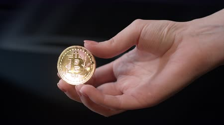 cryptocurrency : Woman hand holding gold bitcoin coin. Bitcoin business concept. Close up of bit coin in hand. Investment in bitcoin cryptocurrency business. Global blockchain technology Stock Footage