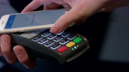 leitor : Payment transaction with smartphone. Hand of customer paying through mobile phone over pos terminal with NFC technology. Wireless money transfer with smartphone app. Smart mobile device at terminal
