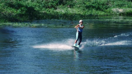 интерн : Pretty girl wakeboarding on summer river. Young girl riding water ski. Woman practicing water skiing. Slim girl wakeskier training riding on water board. Healthy lifestyle concept