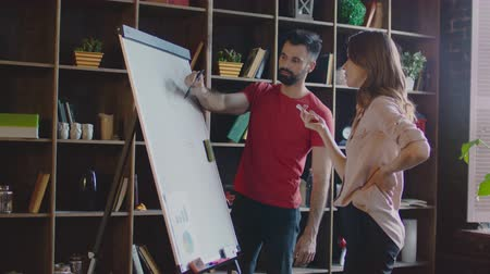 flip chart : Creative team discussing business plan on marker board in office. Teamwork concept. Office workers brainstorming ideas on white board in studio. Business people discussion business strategy Stock Footage