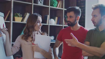 flip chart : Successful business team brainstorming on meeting in creative office. Three business people in office. Creative business people discussing company strategy. Startup team discussion future business Stock Footage