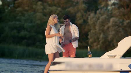 szampan : Happy girl dancing on yacht. Young lovely couple have fun on yacht. Celebration of love. Love couple relaxing on boat. Romantic date on nature