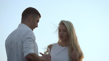 alkol : Young people toasting champagne at sunset. Smiling lovely couple holding glasses with champagne and looking at each other. Happy lovers celebrating anniversary. Romantic dating at sunset Stok Video