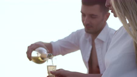 amoroso : Handsome man pouring champagne in wineglasses at sunset. Happy love couple relaxing outdoor. Romantic date with champagne at sunset
