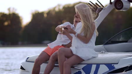 veleiro : Luxury vacation on yacht on lake. Young people boating on yacht at sunset. Love couple relaxing with glass of wina on boat at sunset. Romantic dating outdoors at sunset