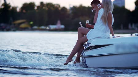 моторная лодка : Beautiful young couple drinking champagne on floating boat. Love story concept. Luxury outdoors vacation on powerboat. Romantic date on river in evening. Love couple relaxing on floating yacht