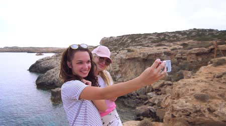 make friends : Pretty girls make selfie photo on sea in slow motion. Happy friends taking self portrait with phone. Cheerful women make selfie photo on smart phone at sea beach