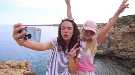 self portrait photography : Beautiful girls taking selfie photo on mobile phone at cyprus beach. Two modern girls posing for selfie picture. Happy woman selfie portrait with v sign hand. Woman photo on mobile