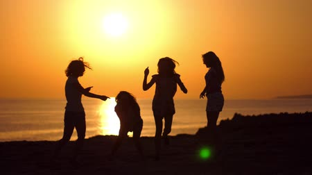bachelorette party : Dancing girls silhouettes at beach sunset. Playful girls enjoying beach party in gloaming. Bachelorette party at seacoast. Tomorrow married. Women silhouettes in evening sunset. Cyprus beach party Stock Footage
