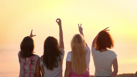 kypr : Young woman showing love sign at sunset. Woman friends enjoy summer vacation. Summer women showing word love with hands. Back view of girls friends relaxing on sunset