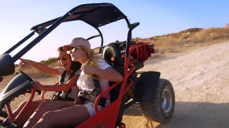 extremely : Two girlfriends extremely spend holidays driving quadricycle in slow motion. Active women driving buggy car. Young women controlling beach buggy. Courageous women. Extreme ride