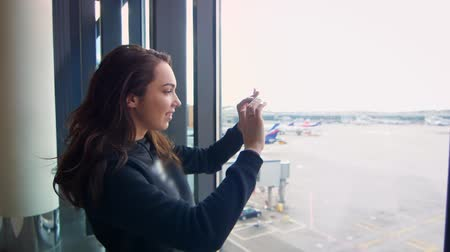 darling : Modern girl taking film on phone departure of plane at airport throught window in slow motion. Young woman make video with her smartphone