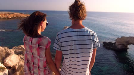 abyss : Just married couple enjoy ocean landscape. Happy honeymoon couple. Back view of romantic couple looking evening sea landscape. Stylish man with woman enjoy rocky beach view. Summer vacation concept