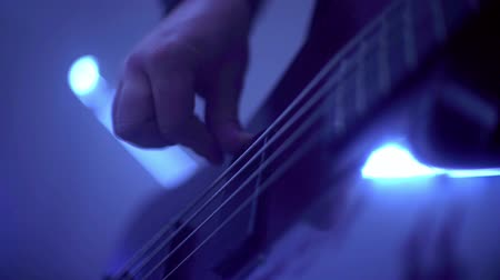 gitáros : Human hands playing on electric guitar. Close up of rock musician playing guitar on stage with scenic illumination. Bassist playing electric bass guitar. Fingers on guitar strings Stock mozgókép