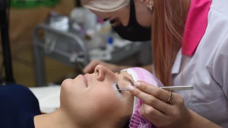 foreigner : Professional beautician undergoing eyelash extension procedure. Master and a client in a modern beauty salon