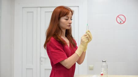 injetar : A young nurse with red hair in red medical clothes dials into a disposable syringe medicine from a glass bottle. Veterinarian.