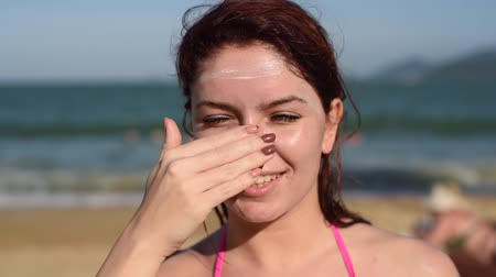 melisa : Portrait of a beautiful young woman, smiling, in a bikini, smeared face with sun protection cream, sea background. Female Applying Sun Cream on face. sunburn. Stok Video